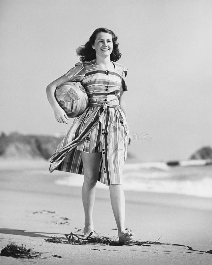 Woman walking on beach carrying ball royalty free stock photo