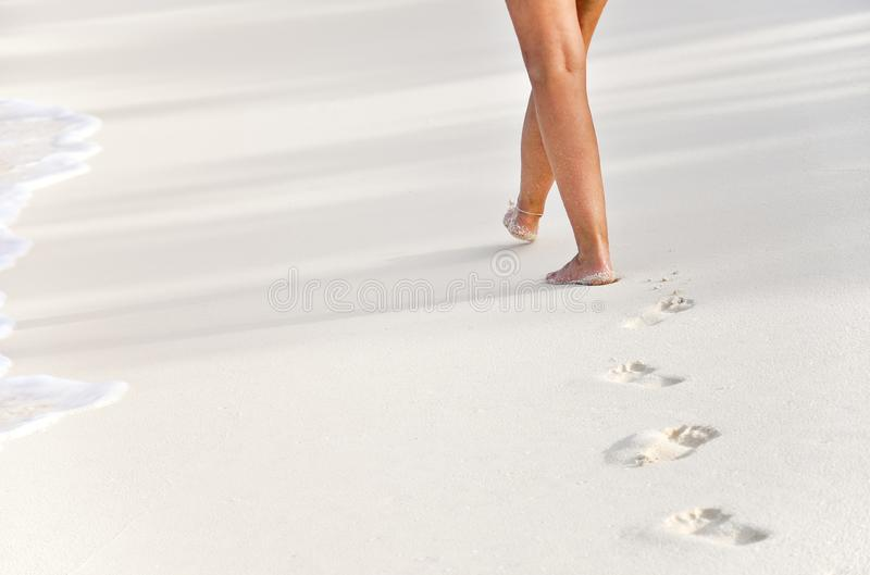 Woman walking on a beach with footprints stock photos