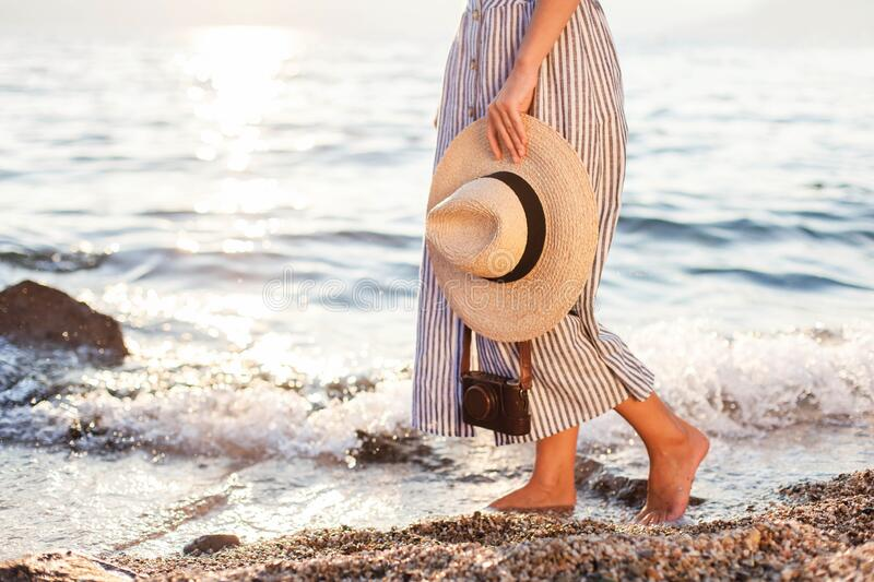 Woman is walking on beach in sea waves. Summer background of sunset ocean. Girl in dress with straw hat and photo camera royalty free stock image
