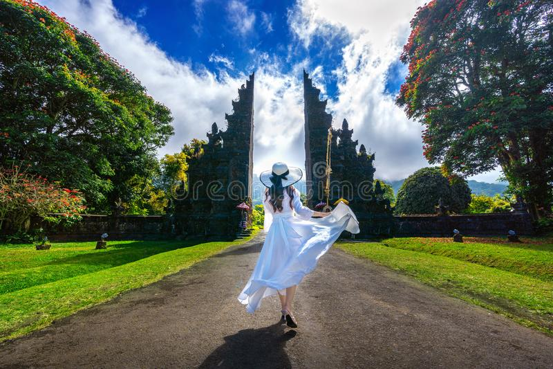 Woman walking at big entrance gate, Bali in Indonesia. stock photography