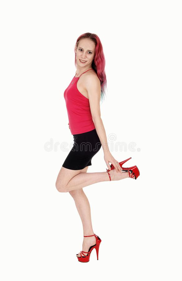 Woman walking in a black skirt and red blouse holding heel. A lovely young woman walking in a black skirt and red top with.her red hair, smiling, isolated for royalty free stock image