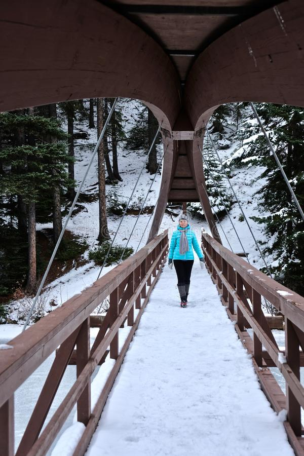 Woman walking on bridge over the frozen river. stock photo