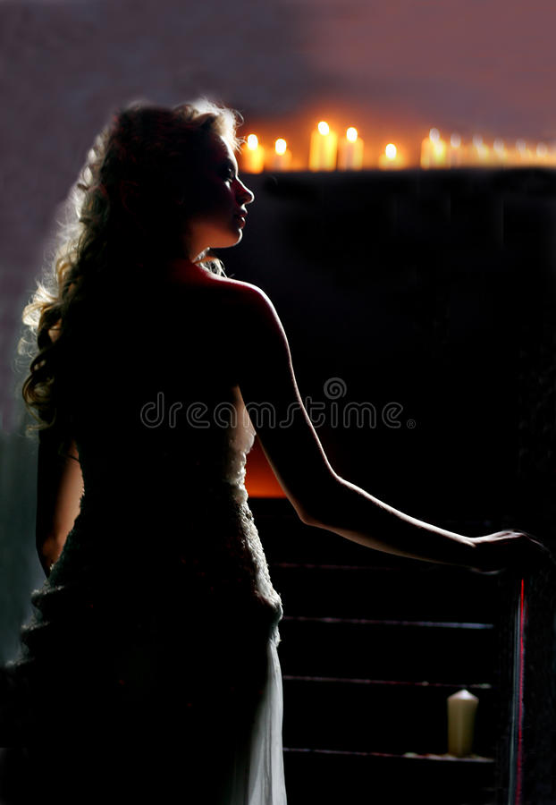 Woman walking in candlelit church royalty free stock images