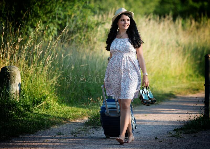 Woman Walking While Carrying Shoes and Luggage Bag during Daytime royalty free stock photos