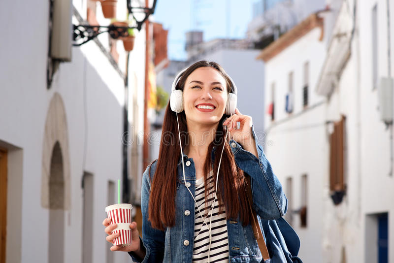 Woman walking on city street with drink and headphones royalty free stock photo