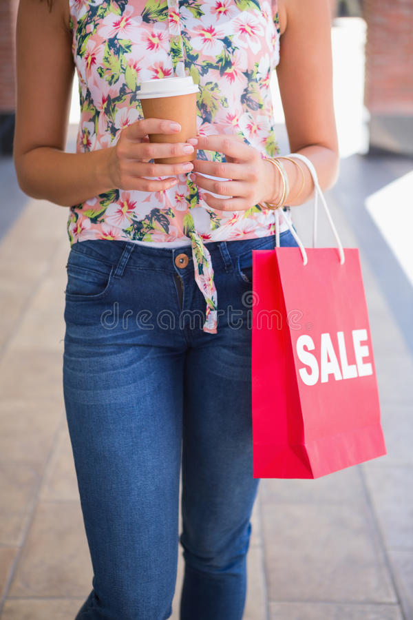 Woman walking with coffee to go and shopping bag royalty free stock photo