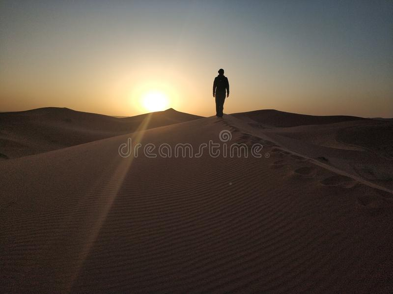 Woman  walking on desert dunes ridge sunrays at sunset. A berber man stands alone on desert dunes looking the sunset. The shapes of the sand due to the wind and royalty free stock image