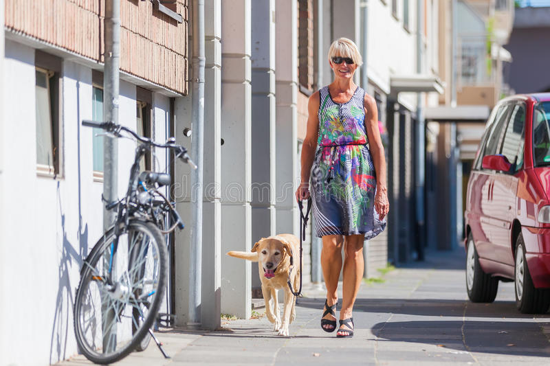 Woman walking with a dog in the city royalty free stock photography