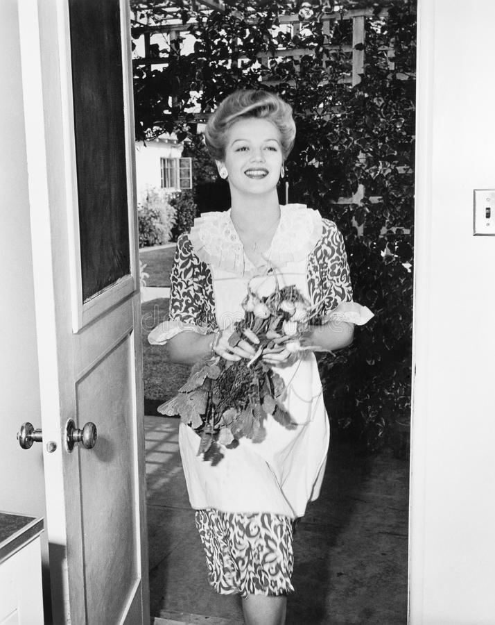 Woman walking through a doorway with flowers in her hands stock image