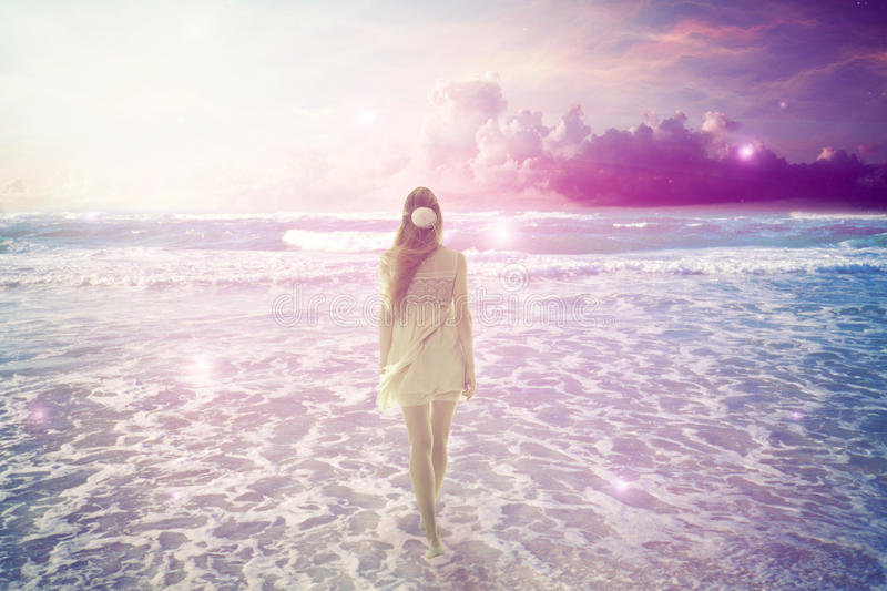 Woman walking on dreamy beach enjoying ocean view. Young woman walking on a dreamy beach enjoying ocean colorful violet sky view. Landscape nature screen saver