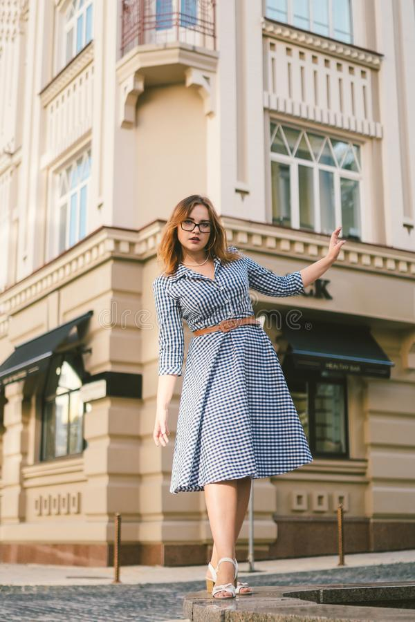 Woman walking in dress in old city. Fashion Style Photo Of A Young Girl. happy stylish woman at old european city street royalty free stock image