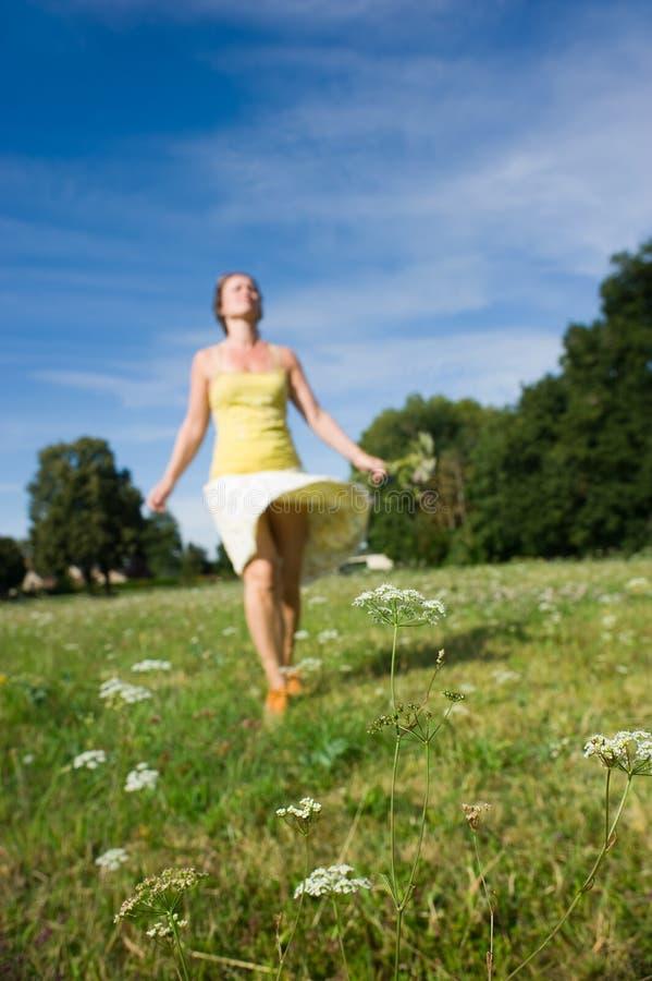 Woman walking in a field royalty free stock image