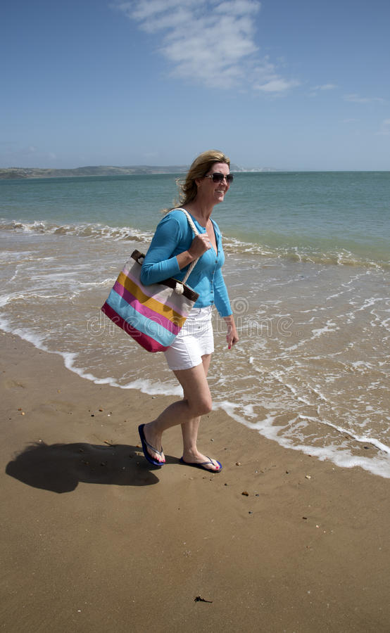 Woman walking in flip flops on a beach. Woman wearing flip flops carrying beach bag walking on the beach Southern England UK stock photo