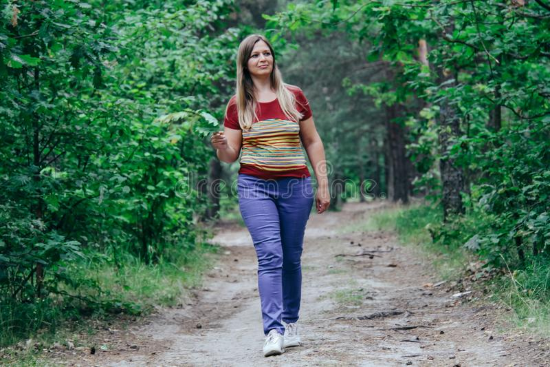 Woman walking at the forest. Relaxed middle aged woman walking at the forest stock photography