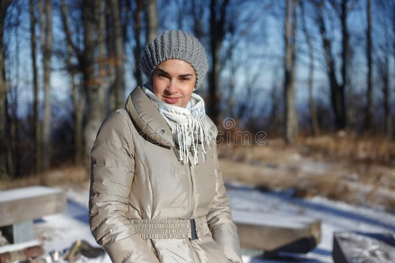 Woman walking in forest in winter. Portrait of smiling woman walking in forest in winter wearing hat scarf and warm coat royalty free stock image