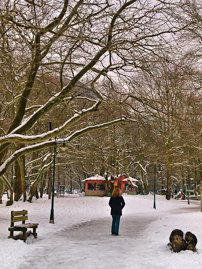 Woman  walking on frozen path, in a park in Naousa, Greece. Snow covered Agios Nikolaos & x28;Saint Nicholas& x29; park with benches and paths in Naousa Greece stock image
