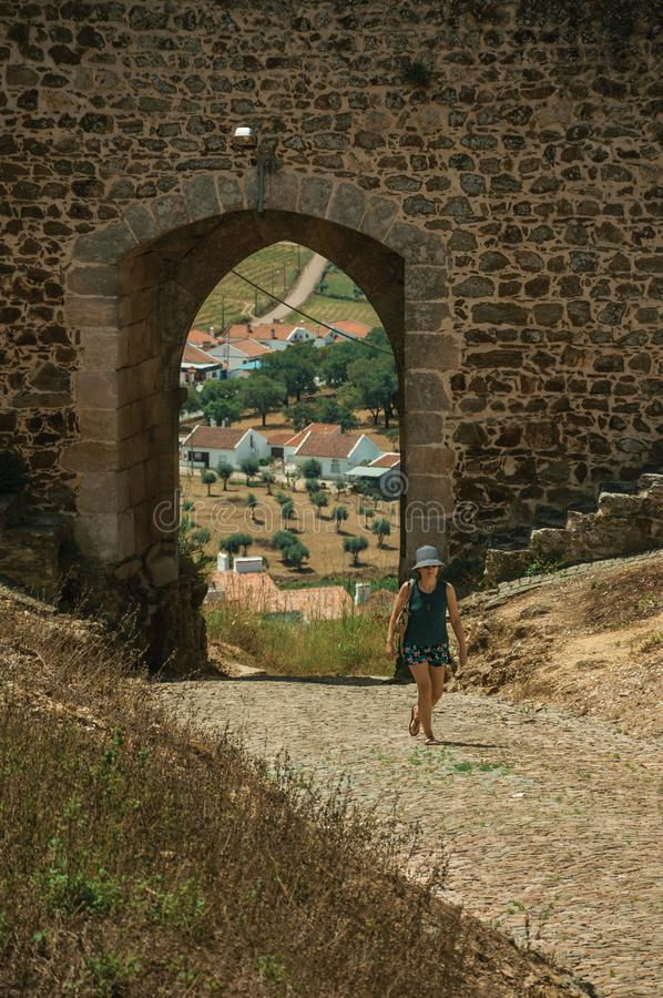 Woman walking through gateway at Evoramonte royalty free stock photos
