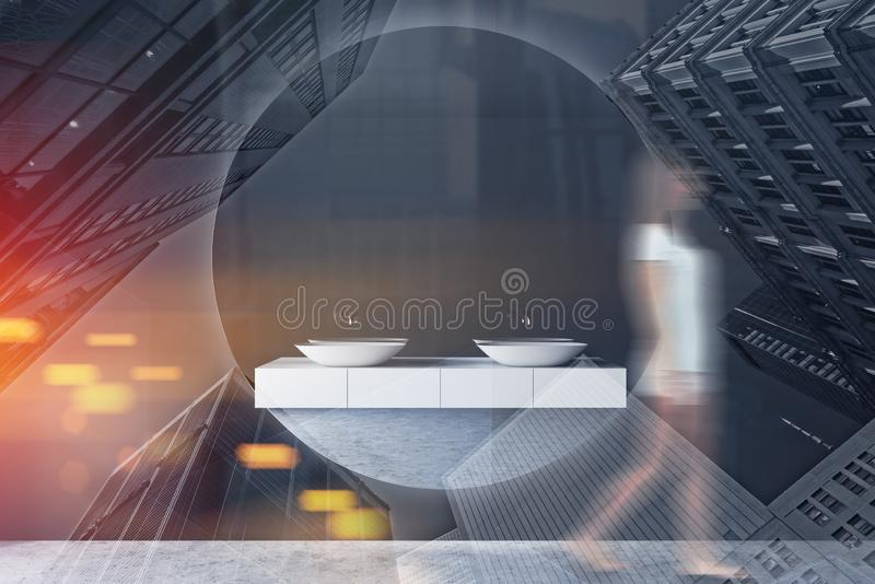 Woman walking in gray bathroom with double sink. Young woman in casual clothes walking in luxury bathroom interior with gray walls, concrete floor, double sink royalty free stock photography