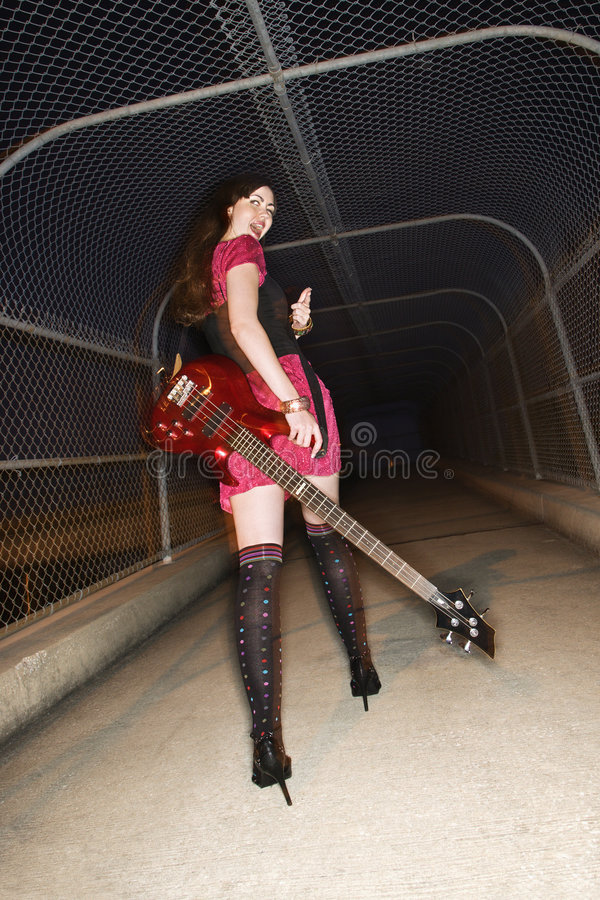 Woman walking with guitar. royalty free stock photography