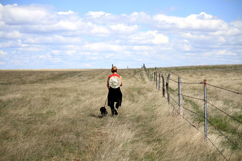 Woman walking her dog on the prairies of South Dakota. stock photos