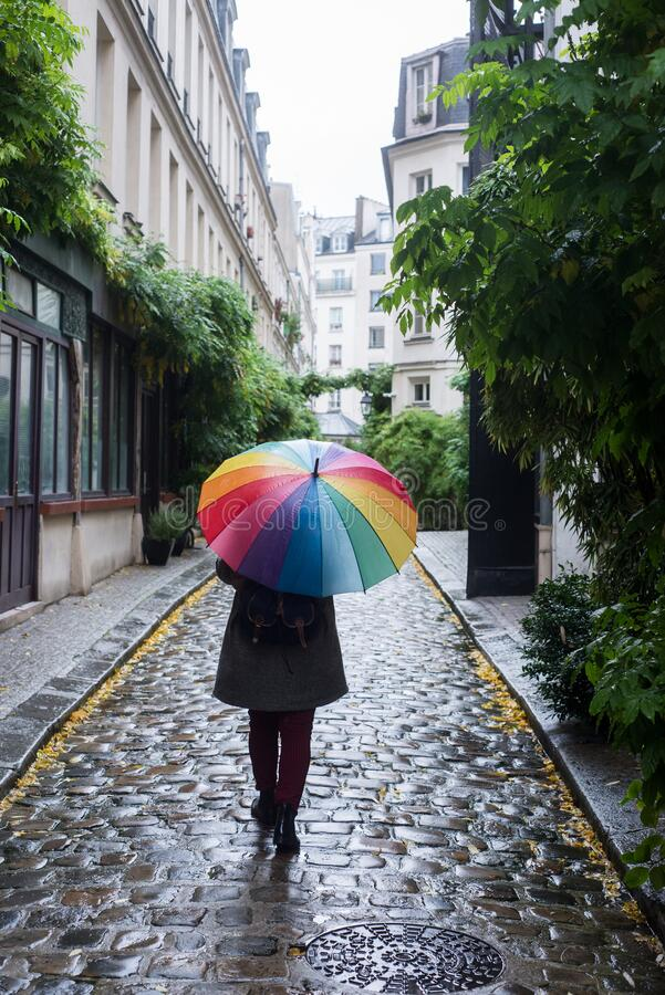 Free Woman Walking In The Cobbelstone Street With A Rainbow Umbrella Royalty Free Stock Photo - 221244935