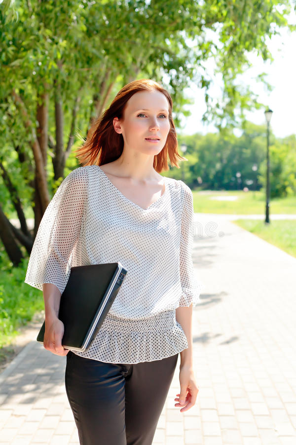 Woman walking with laptop royalty free stock photo