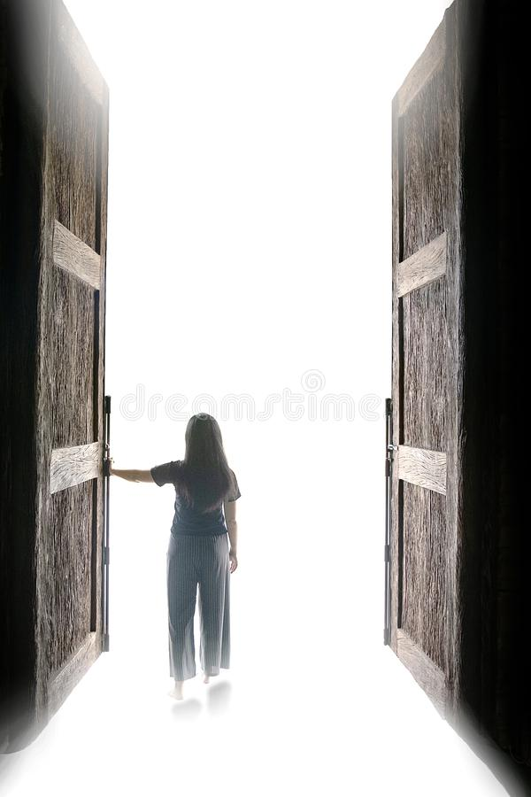 Woman walking into the light through open big door, to go to nirvana, every cloud has a silver lining, stock image