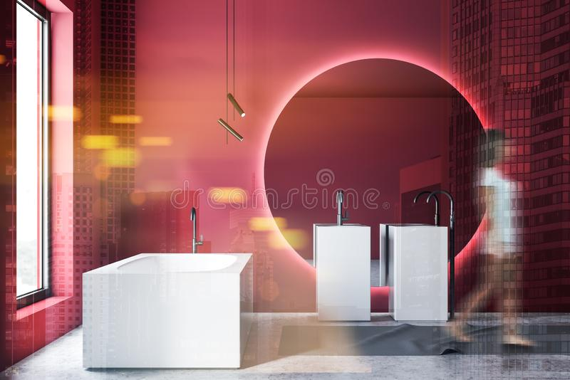 Woman walking in luxury red bathroom. Young woman in casual clothes walking in luxury bathroom with red walls, concrete floor, double sink with large round stock photography