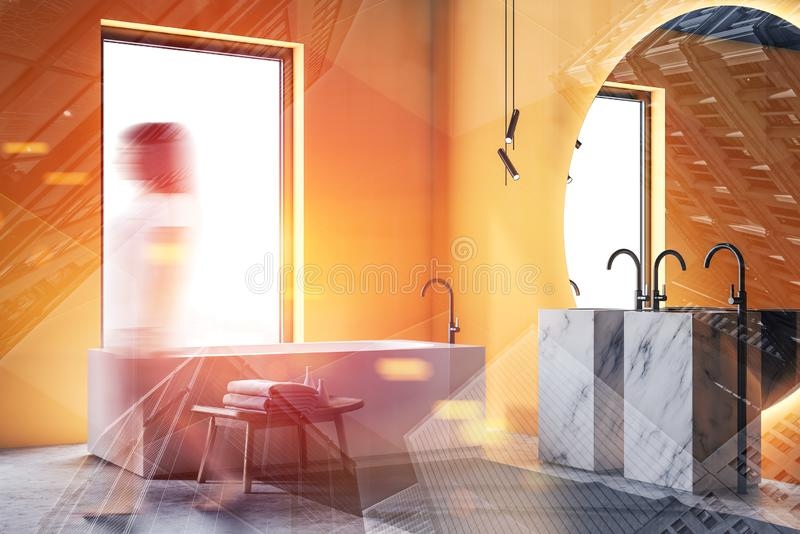 Woman walking in luxury yellow bathroom. Young woman in casual clothes walking in luxury bathroom with yellow walls, concrete floor, double marble sink with stock photos
