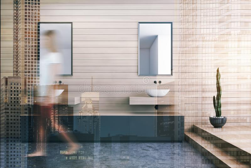 Woman walking in wooden bathroom with sinks royalty free stock photo