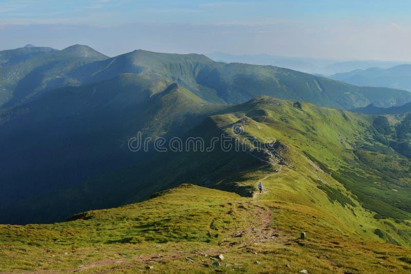 Woman walking on mountain path stock photos