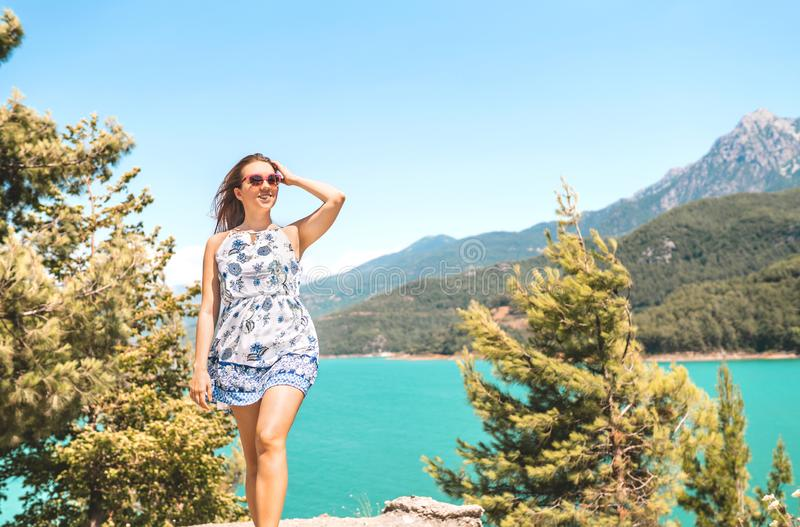 Woman walking in nature, mountain in the background. Adventure, freedom and carefree lifestyle. Millennial lady in summer dress. stock image