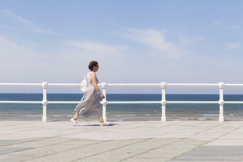 Woman walking near the beach royalty free stock photos