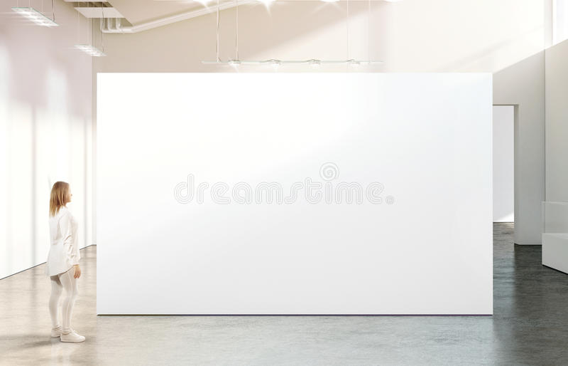 Woman walking near blank white wall mockup in modern gallery royalty free stock image