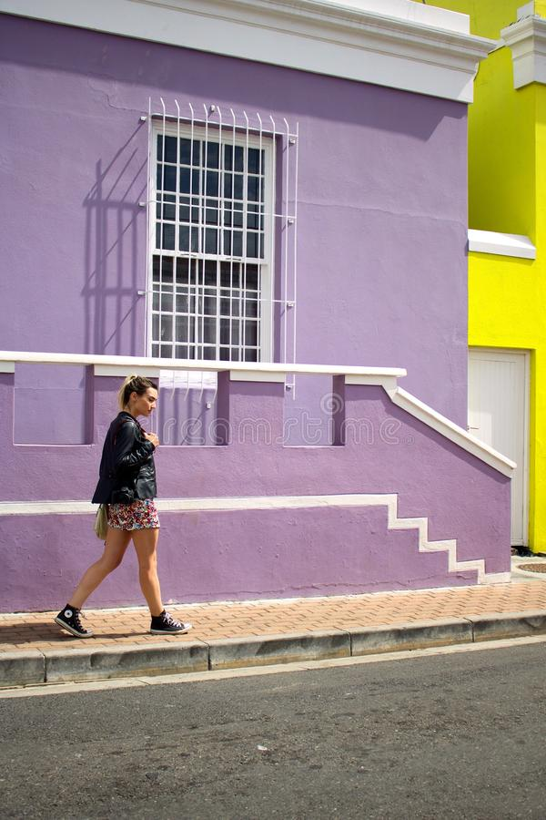 Woman Walking Near Purple Painted Building stock images