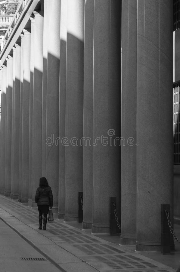 Woman walking close to colonnade royalty free stock images