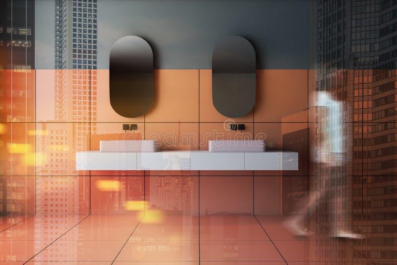 Woman walking in orange and gray bathroom, sink royalty free stock photo