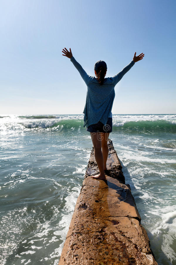 Woman walking out onto break wall with waves of ocean in front royalty free stock photo
