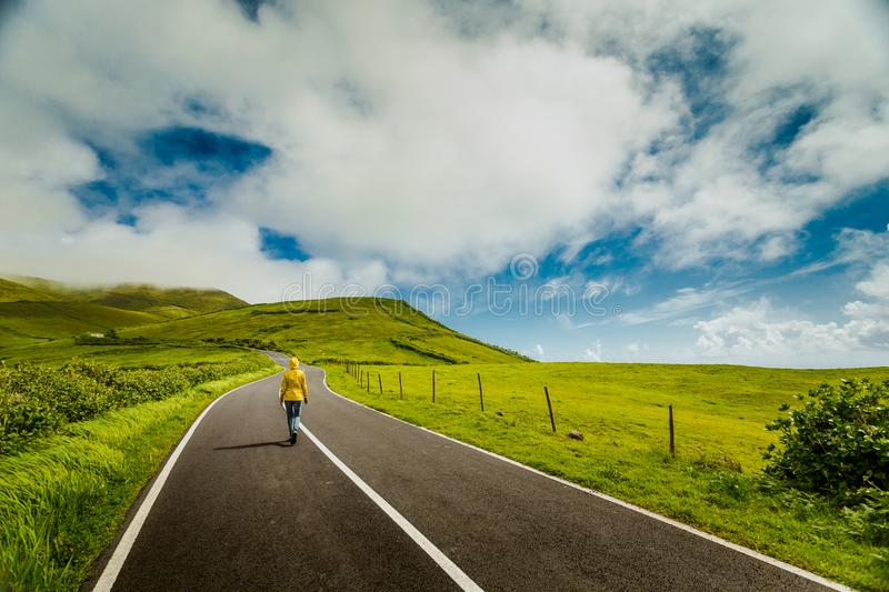 Woman walking over a beautiful road. Woman walking on a beautiful road on Flores Island, Azores, Portugal royalty free stock image