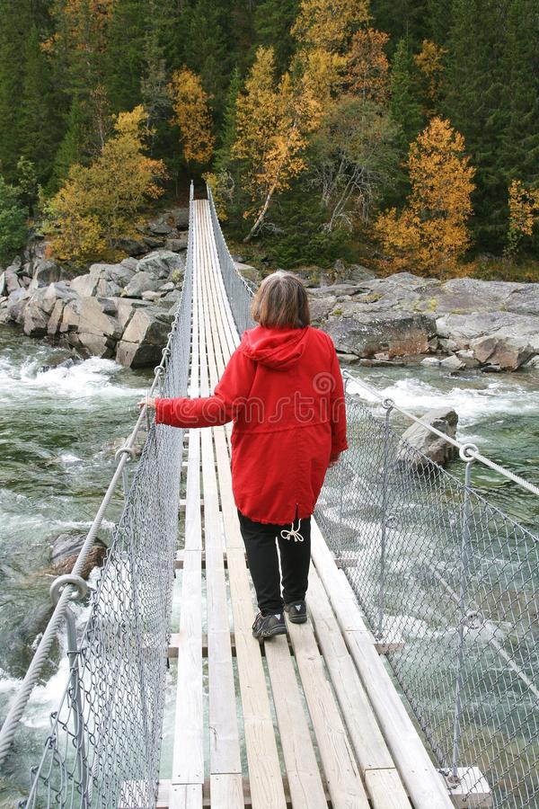 Woman walking over a suspension bridge royalty free stock image