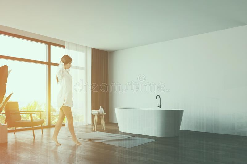 Woman walking in panoramic white bathroom. Beautiful young woman in nightgown walking in luxury panoramic bathroom with white walls, wooden floor, comfortable royalty free stock photos
