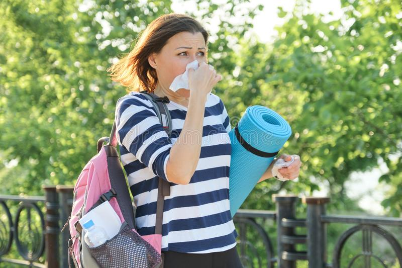 Woman walking in the park with handkerchief, coughing and sneezing stock photos