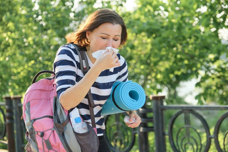 Woman walking in the park with handkerchief, coughing and sneezing stock images