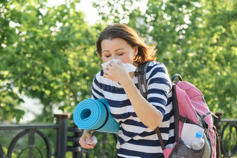 Woman walking in the park with handkerchief, coughing and sneezing royalty free stock images