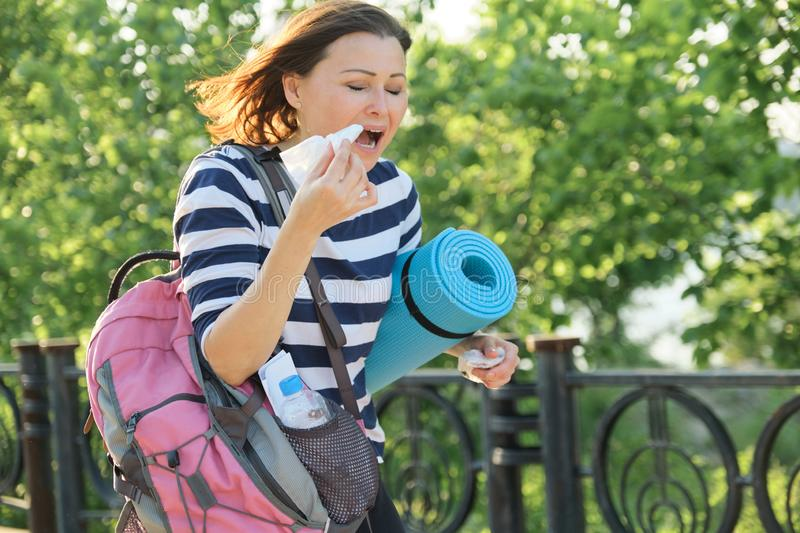 Woman walking in the park with handkerchief, coughing and sneezing royalty free stock photography