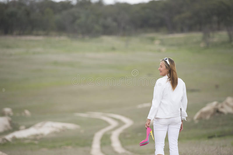 Woman walking in park holding high heel shoes. Portrait of attractive mature woman walking down winding dirt track through grass field, wearing white cloths and royalty free stock image