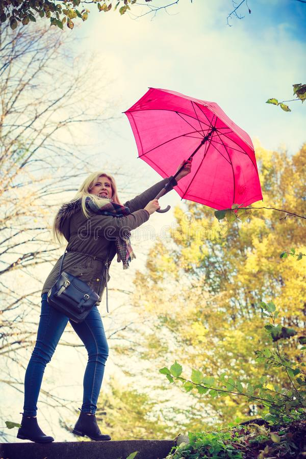 Woman walking in park with umbrella, strong wind stock images