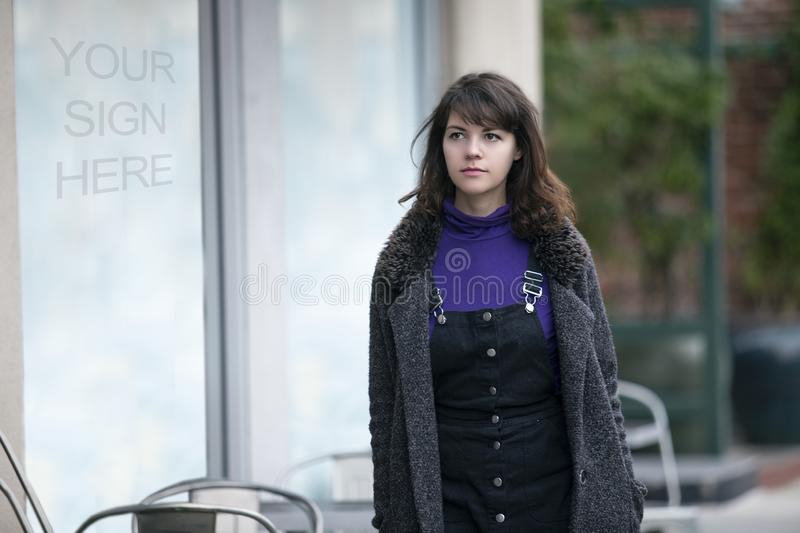 Woman Walking Past a Store Window Sign royalty free stock photos