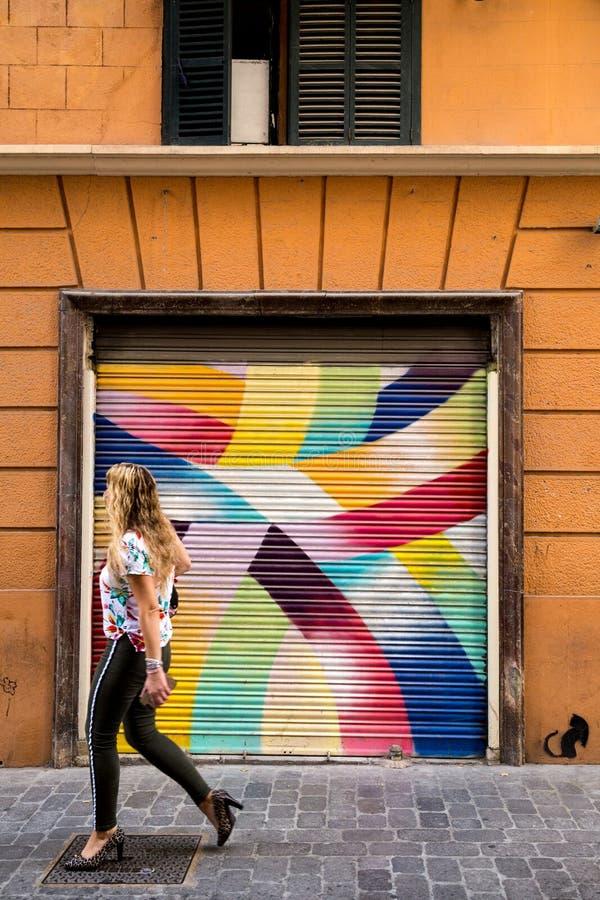 Woman walking past urban street art in Palma de Mallorca, Spain. A stylish woman walks down the cobblestone streets of Palma de Mallorca, Spain, passing by one stock photo