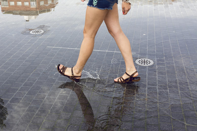 Woman walking on a puddle in the street royalty free stock photos
